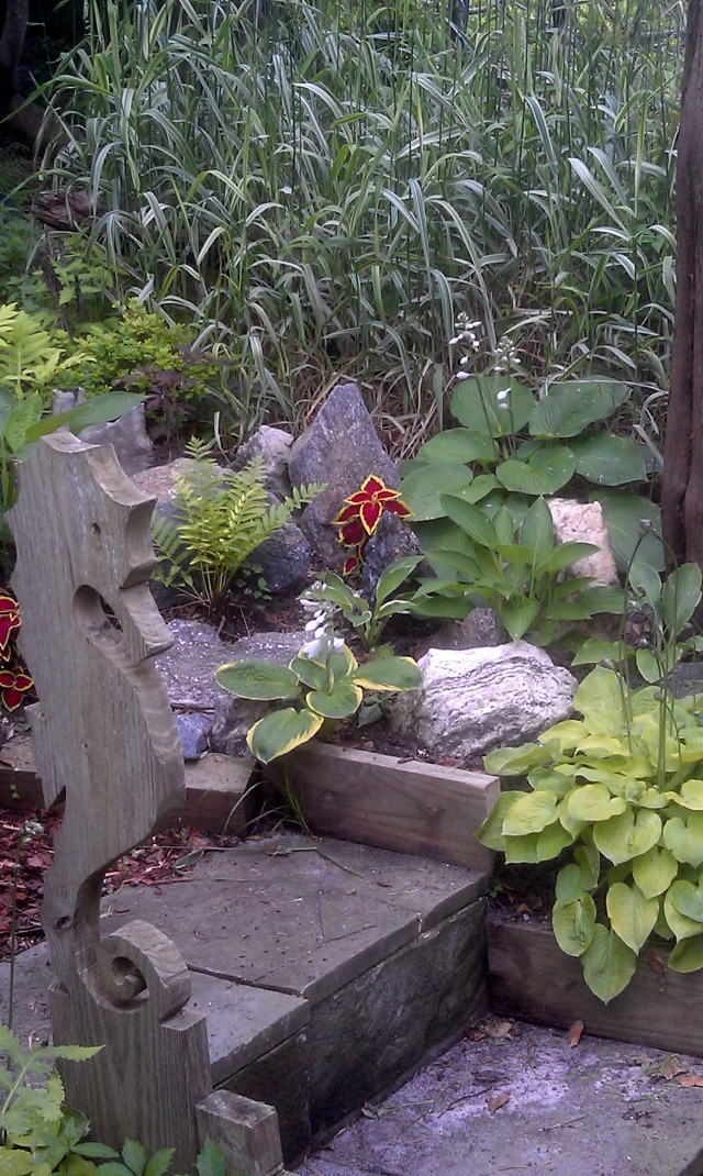 A close-up of the rock garden with varigated grasses behind and slate steps leading up from the hot tub patio.