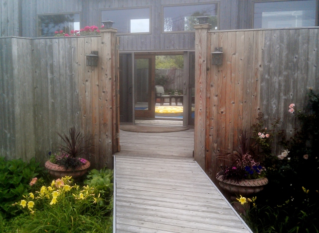 I'm starting with this photo to help you get oriented. Our entry starts with a bridge a few feet off the ground that leads from the wooden walk outside (all Fire Island houses are located along wooden walks; no cars are allowed here) to the gate leading into our front deck.
